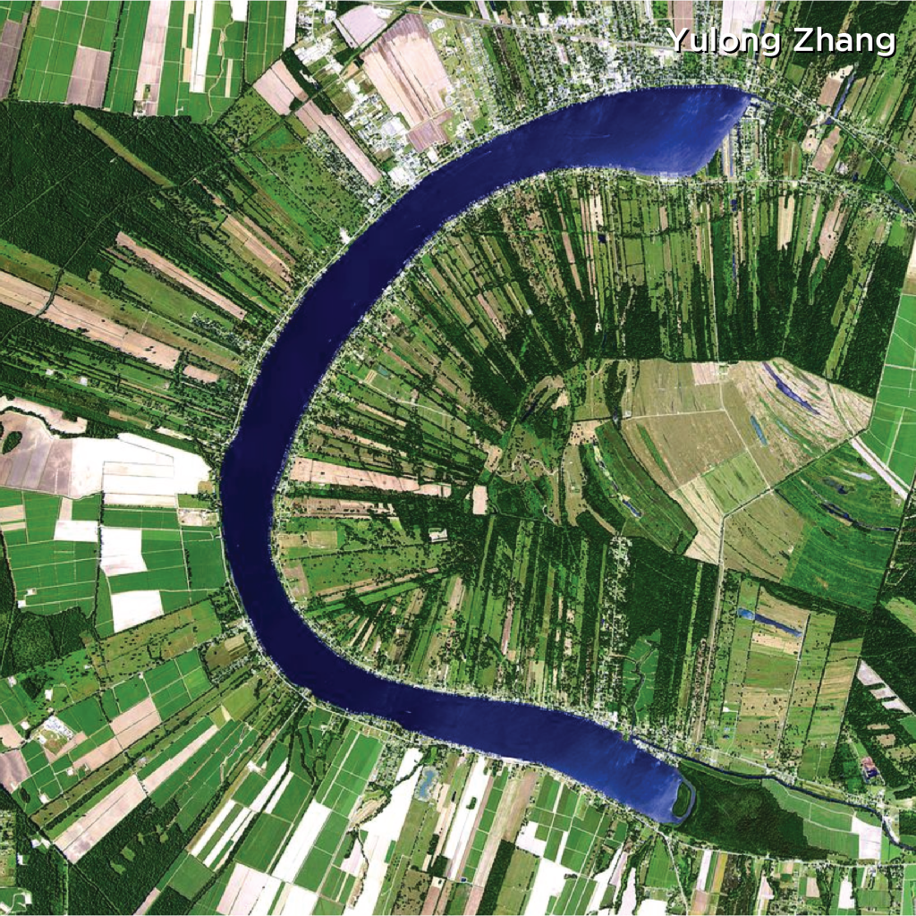 Satellite image of the False River in Louisiana with narrow slices of farmland fanning out along a crescent of water that is the thickness of a river.